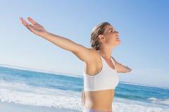 Sportliche blonde Stellung auf dem Strand mit den Armen heraus Stockbilder