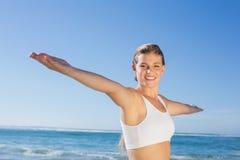 Sportliche blonde Stellung auf dem Strand mit den Armen heraus Lizenzfreie Stockbilder