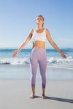 Sportliche blonde Stellung auf dem Strand mit den Armen heraus Stockfoto