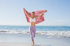 Sportliche blonde Stellung auf dem Strand mit einem Schal Lizenzfreie Stockfotos