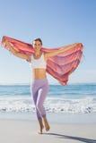 Sportliche blonde Stellung auf dem Strand mit einem Schal Stockfotos