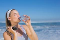 Sportliche blonde Stellung auf dem Strand mit Flasche und Springseil Stockbilder