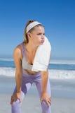 Sportliche blonde Stellung auf dem Strand mit Tuch Lizenzfreie Stockfotos