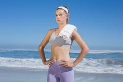 Sportliche blonde Stellung auf dem Strand mit Tuch Stockfotos