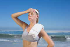 Sportliche blonde Stellung auf dem Strand mit Tuch Stockbild