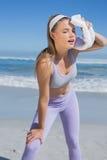Sportliche blonde Stellung auf dem Strand mit Tuch Lizenzfreie Stockbilder