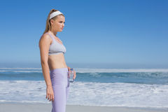 Sportliche blonde Stellung auf dem Strand mit Wasserflasche Lizenzfreie Stockfotografie