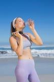 Sportliche blonde Stellung auf dem Trinkwasser des Strandes Lizenzfreies Stockbild