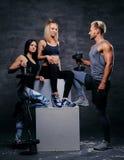 Sportliche blonde und Brunettefrauen und ein athletischer Mann über grauem Ba Lizenzfreie Stockbilder