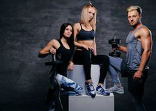 Sportliche blonde und Brunettefrauen und ein athletischer Mann über grauem Ba Stockfoto