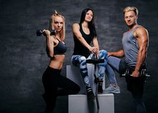 Sportliche blonde und Brunettefrauen und ein athletischer Mann über grauem Ba Lizenzfreie Stockfotografie