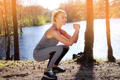 Sportliche blonde weibliche Handelnhocken Lizenzfreies Stockbild