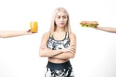 Sportliche Blondine lehnt Schnellimbiß ab stockfoto