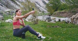 Sportliche Dame nach dem Training mitten in überraschender Landschaftsansicht die Zeit mit genießend selfies mit nehmend