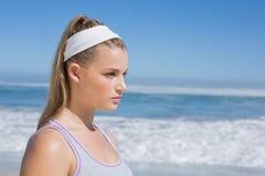 Sportliche ernste blonde Stellung auf dem Strand Stockfotos