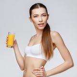 Sportliche Frau über dem grauen Hintergrund, der Glas Orangensaft hält Lizenzfreies Stockbild