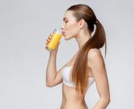 Sportliche Frau über dem grauen Hintergrund, der Glas Orangensaft hält Stockbild