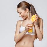 Sportliche Frau über dem grauen Hintergrund, der Glas Orangensaft hält Stockbilder