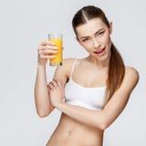 Sportliche Frau über dem grauen Hintergrund, der Glas Orangensaft hält Stockfotos