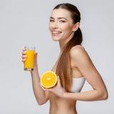 Sportliche Frau über dem grauen Hintergrund, der Glas Orangensaft hält Stockfoto