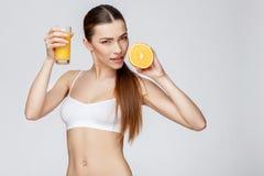 Sportliche Frau über dem grauen Hintergrund, der Glas Orangensaft hält Lizenzfreies Stockfoto