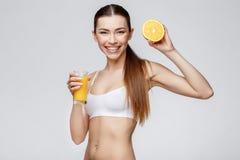 Sportliche Frau über dem grauen Hintergrund, der Glas Orangensaft hält Lizenzfreie Stockbilder