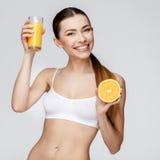 Sportliche Frau über dem grauen Hintergrund, der Glas Orangensaft hält Stockfotografie