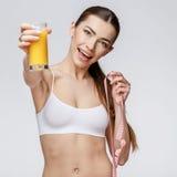 Sportliche Frau über dem grauen Hintergrund, der Glas Orangensaft hält Lizenzfreie Stockfotografie