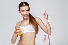 Sportliche Frau über dem grauen Hintergrund, der Glas Orangensaft hält Lizenzfreie Stockfotos