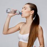 Sportliche Frau über Trinkwasser des grauen Hintergrundes Lizenzfreies Stockfoto