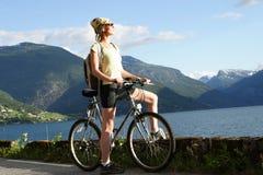 Sportliche Frau auf einer Fahrradreise in den Bergen 2 Stockbild