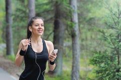 Sportliche Frau der gesunden Lebensstileignung mit dem Kopfhörer, der herein läuft Lizenzfreies Stockbild