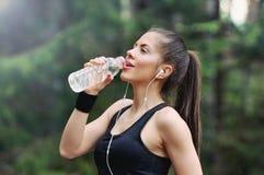 Sportliche Frau des gesunden Lebensstils mit Trinkwasser des Kopfhörers herein Stockbild