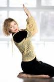 Sportliche Frau, die Übungen mit Yogaelementen in der Klasse tut Stockbild