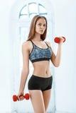 Sportliche Frau, die Aerobic-Übung mit roten Dummköpfen tut Lizenzfreies Stockfoto