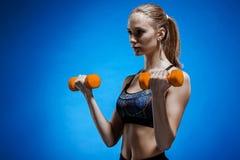 Sportliche Frau, die Aerobic-Übung mit roten Dummköpfen tut Stockfotografie