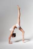 Sportliche Frau, die auf Brücke mit dem Bein oben steht Stockfotografie