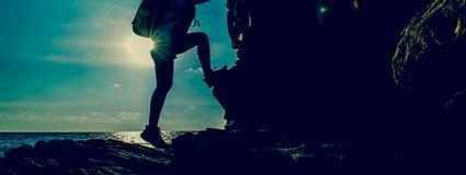 Sportliche Frau, die auf der Klippe klettert stockbilder
