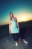 Sportliche Frau, die auf einer Straße im Sonnenuntergang steht lizenzfreie stockbilder
