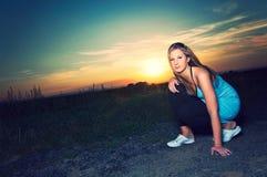 Sportliche Frau, die auf einer Straße im Sonnenuntergang steht stockbild
