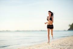 Sportliche Frau, die auf Küste rüttelt stockbilder