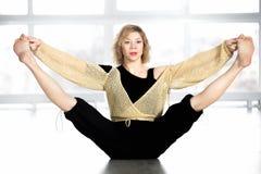Sportliche Frau, die Beine in der Klasse ausdehnend sitzt Lizenzfreie Stockbilder