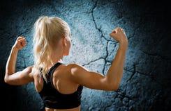 Sportliche Frau, die Bizeps von der Rückseite biegt und zeigt Stockfotos
