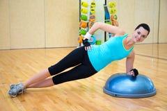 Sportliche Frau, die Übungen für Bauchmuskeln auf bosu Ball tut Lizenzfreie Stockfotos