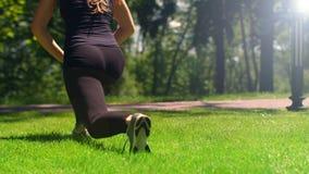 Sportliche Frau, die die Übungen ausdehnend im Freien tut Eignungsmädchen, das Laufleinen tut stock video