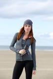 Sportliche Frau, die draußen mit Wasserflasche steht Stockfotos