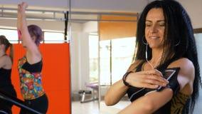 Sportliche Frau, die eine Eignungsverfolger-APP auf Smartphoneanzeige beim Rütteln überprüft stock video