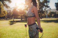 Sportliche Frau, die in einem Park überspringt lizenzfreie stockfotografie