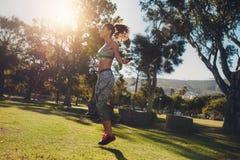 Sportliche Frau, die in einem Park überspringt stockfotos