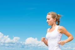 Sportliche Frau, die entlang den Strand läuft Stockfotografie